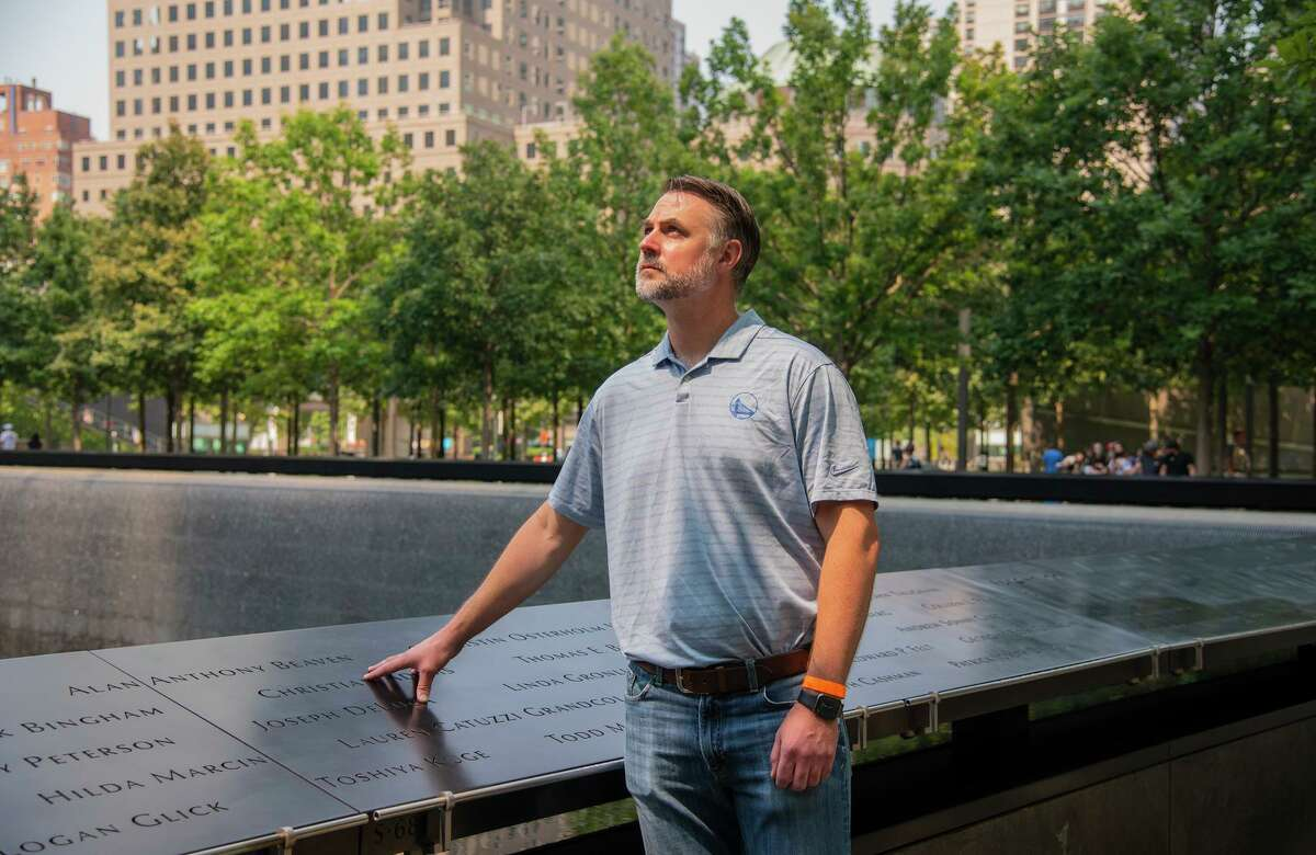 NEW YORK - John Beaven stands where his father's name is engraved at the 9/11 Memorial in Manhattan, New York on July 27, 2021.