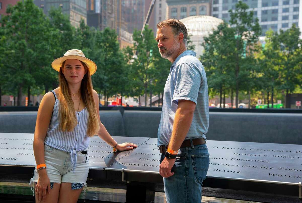 John Beaven and his daughter Sara, 16, stands where his father's name is engraved at the 9/11 Memorial in Manhattan, New York on July 27, 2021.