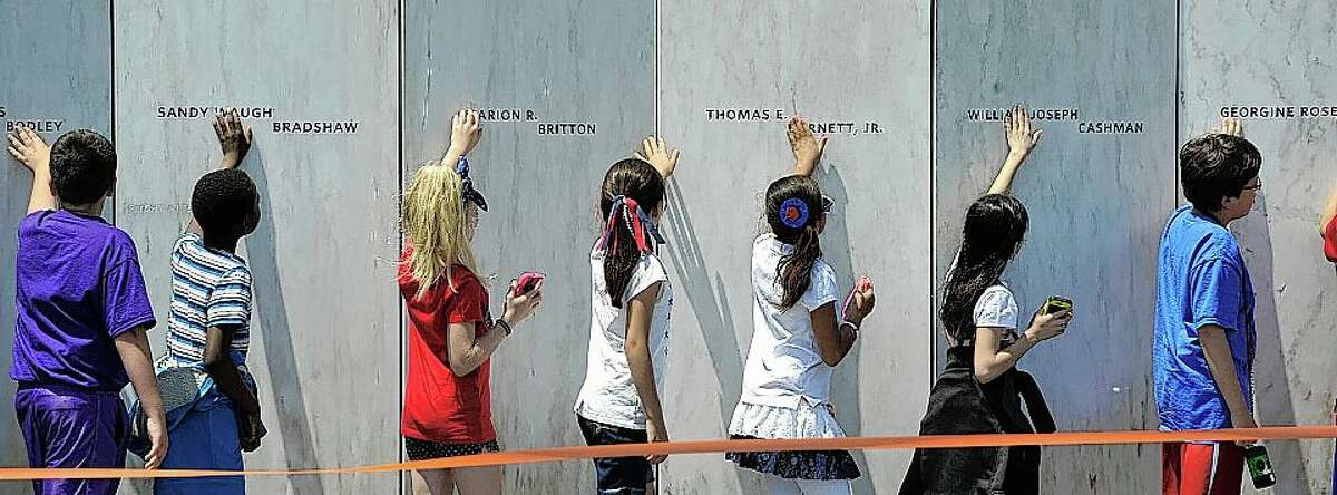 """Students touch the """"wall of names"""" at the Flight 93 Memorial in Shanksville, Pennsylvania."""