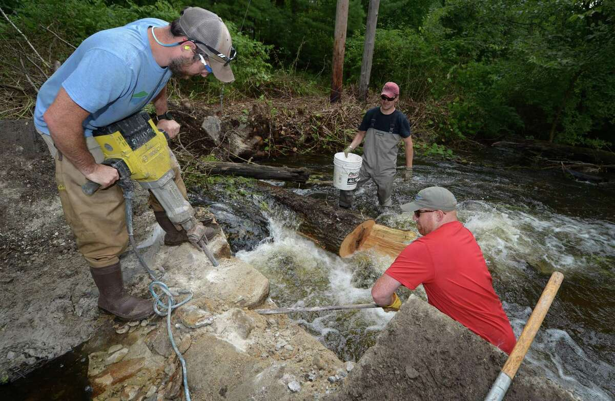 Representatives of DEEP including Peter Grundy and employees of Trout Unlimited, Bill Doyle and Ben Couch, come together Wednesday, August 15, 2018, to jackhammer open the breach at the Cannondale Dam in Wilton, Conn. The demolition of the dam is part of a larger project to remove dams from the Norwalk river and restore native fish populations.