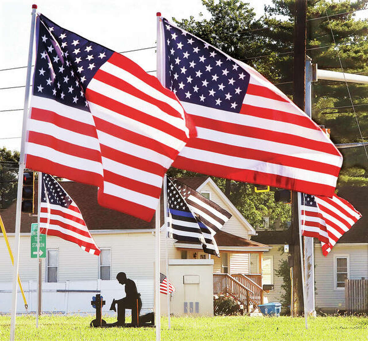 A silhouette cut-out of a kneeling police officer was part of a large flag display this week in front of the Wood River Police station. Flags have been popping up across the area for the 20th anniversary of September 11, 2001, when 2,752 people died, including 37 Port Authority police officers and 23 New York City police officers.