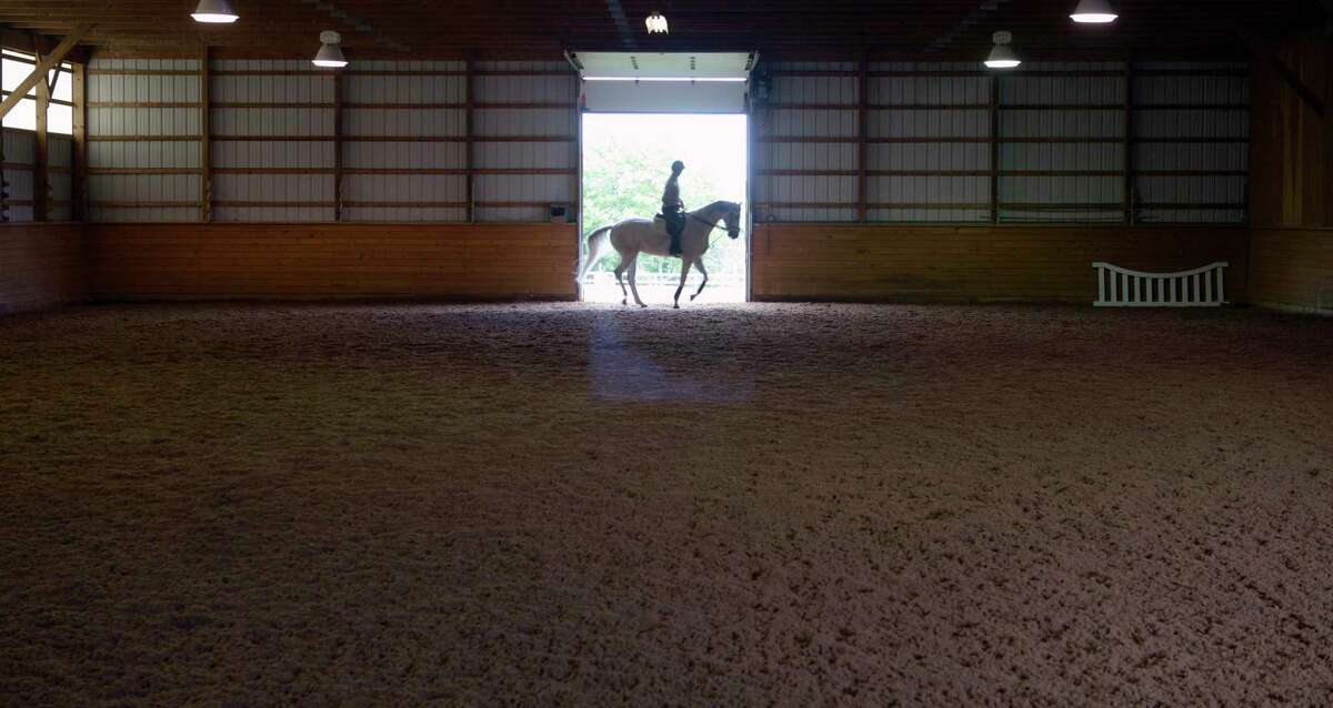 The indoor riding ring of Ridgebury Farm and Stables, an equestrian facility offering hippotherapy and equine-assisted therapy.