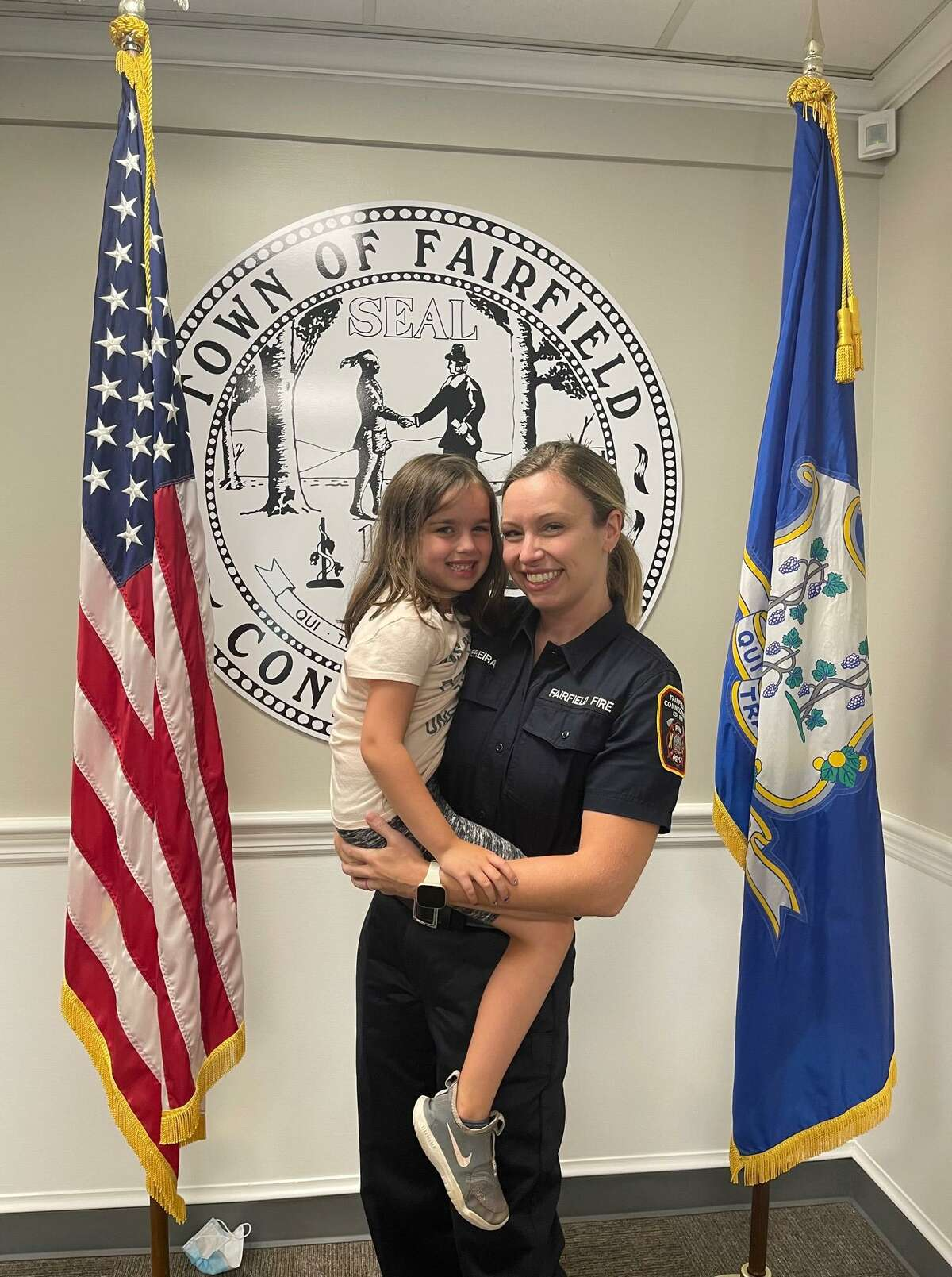 Caitlin Clarkson Pereira, of Fairfield, poses with her daughter after she was sworn in as one of Fairfield's newest firefighters.