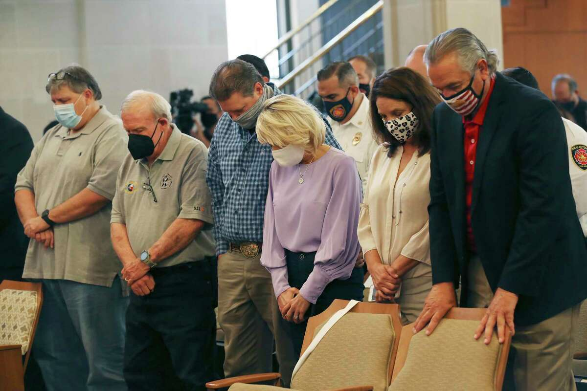 First responders sent to Ground Zero after 9/11 pray with their wives during a ceremony in City Council chambers. From left are René M. Garcia Jr., Dennis Meier, Shane and Tiffany George, and Velma and Frank Willborn.