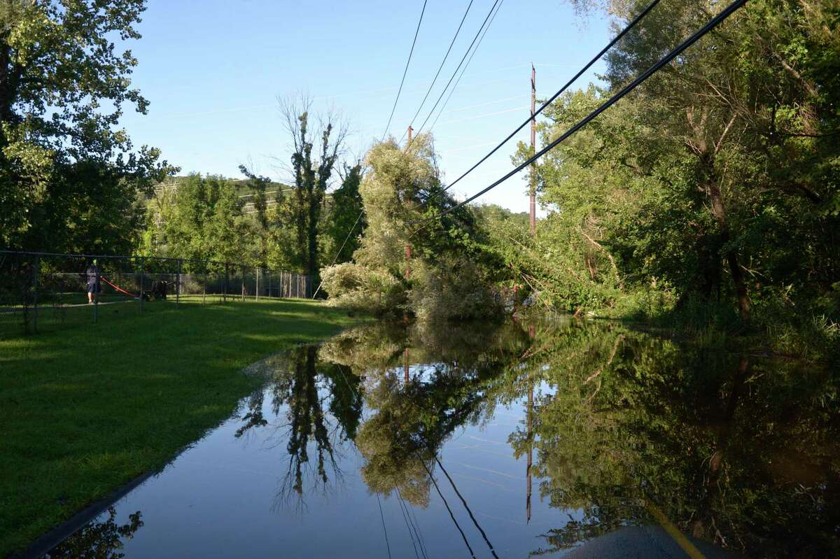 Shelter Rock Road is blocked by a downed tree and flooding of East Swamp Brook in Bethel by Meckauer Park on Thursday morning. Remnants of hurricane Ida brought heavy rain and winds greater than expected by some to the Danbury area, leaving some without power and closing and delaying some school districts. Thursday, September 2, 2021. In Bethel, Conn.