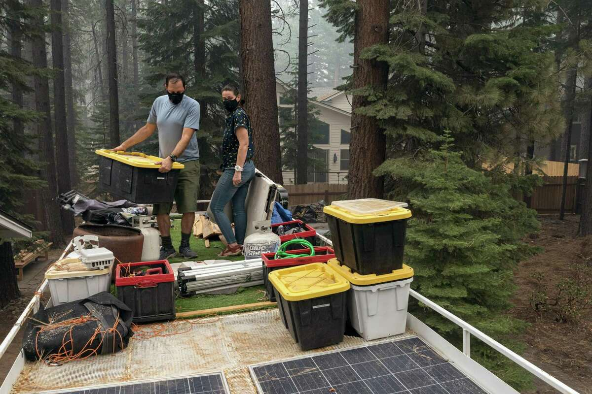 Philipson and Bonetti pack some necessities on the roof of their home, a converted school bus, as they prepare to leave the South Lake Tahoe area on Aug. 27, due to the poor air quality and the threat from the Caldor Fire.