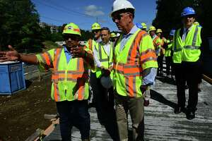 Connecticut Governor Ned Lamont, right, tours the Metro North Danbury Line Merritt 7 train station with construction engineer Emilio Flores Friday, September 10, 2021, in Norwalk, Conn. The governor toured platform with the DOT commissioner and other officials to discuss improvements to the train station.