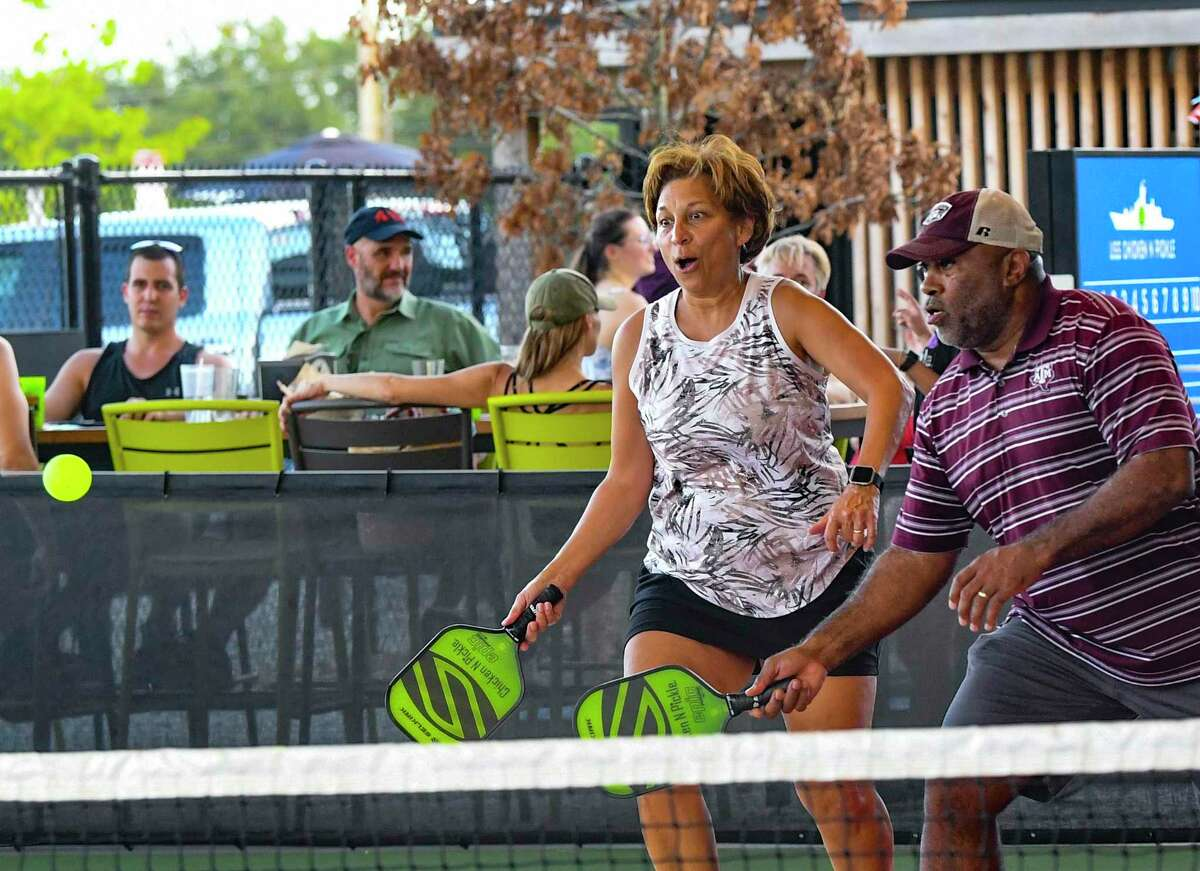 Jimmie and Yvonne Hawkins chase down the ball during a pickleball game at Chicken N Pickle. Young people are increasingly playing games, such as bocce, pickleball, cornhole and shuffleboard, that are typically associated with seniors.
