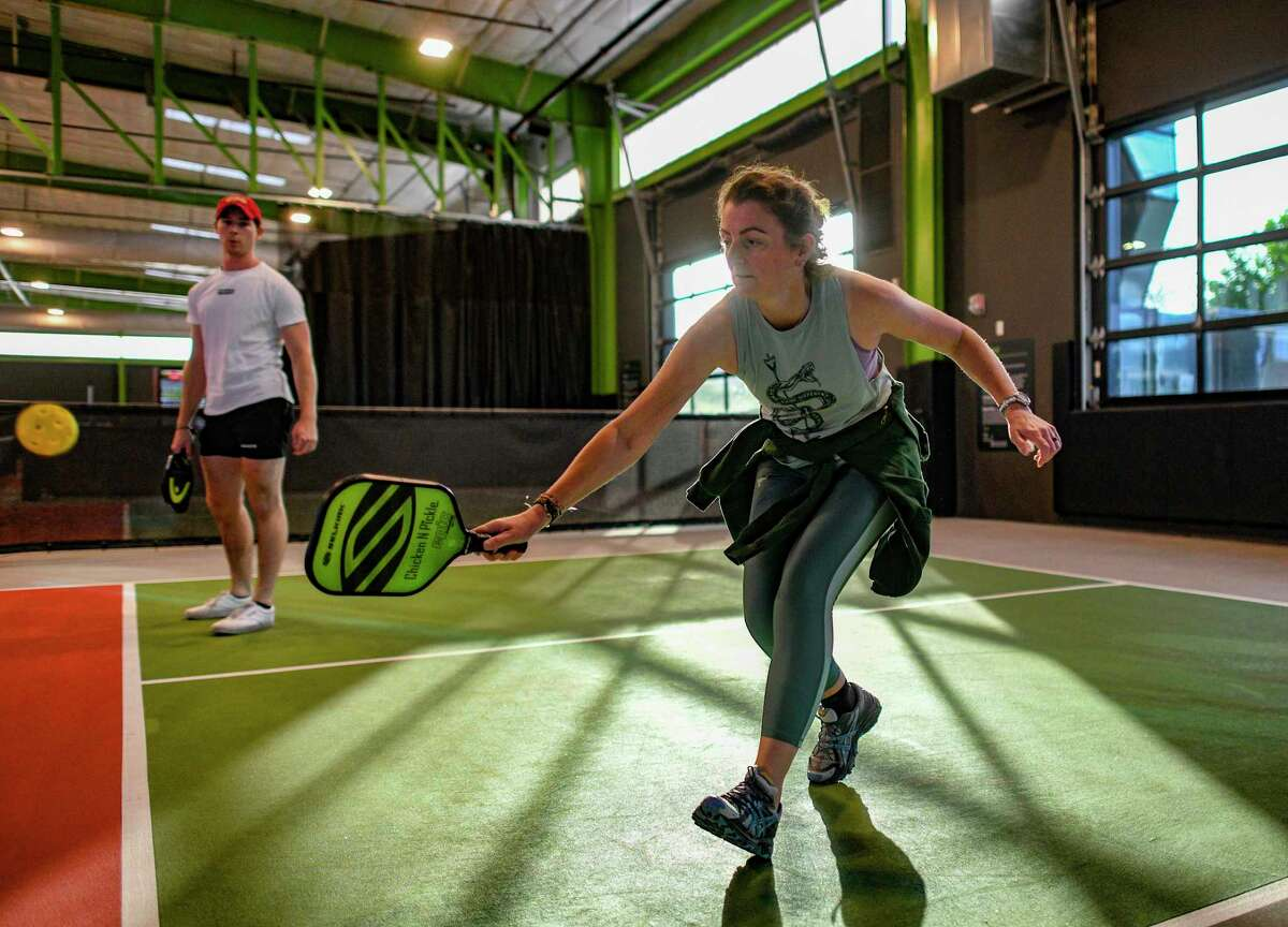 Sarah Scott returns a shot during a pickleball match at Chicken N Pickle. More young people are playing pickleball, making it one of the fastest growing sports in the country.
