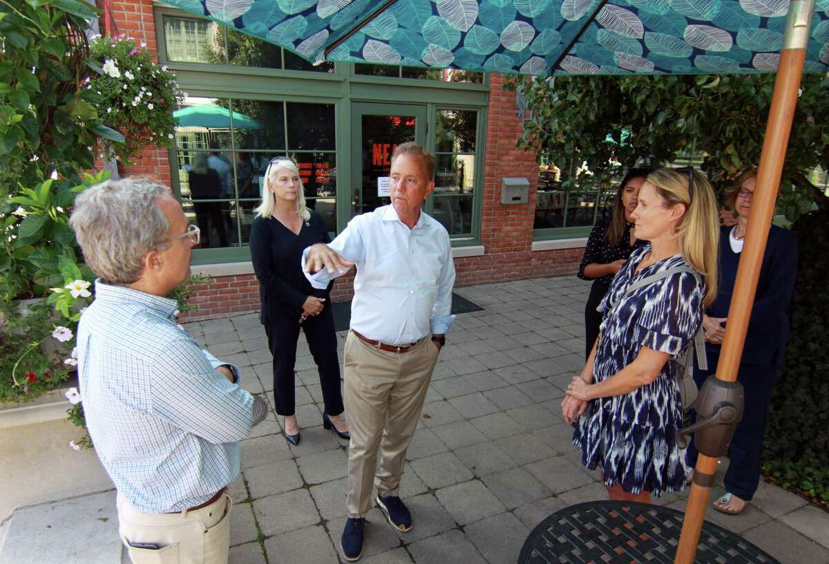 Governor Ned Lamont and First Selectman Jayme Stevenson, in back left, tour businesses that were damaged by flooding from Hurricane Ida in Darien, Conn., on Friday Sentember 10, 2021.