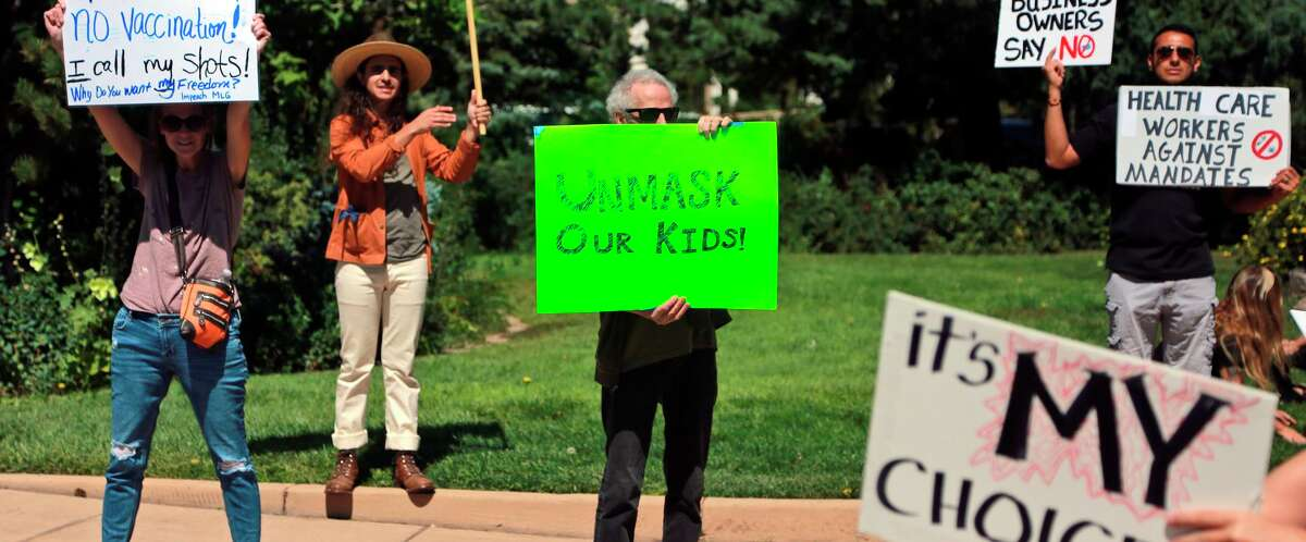 Protesters against COVID-19 vaccine and mask mandates demonstrate near the state Capitol in Santa Fe, N.M.