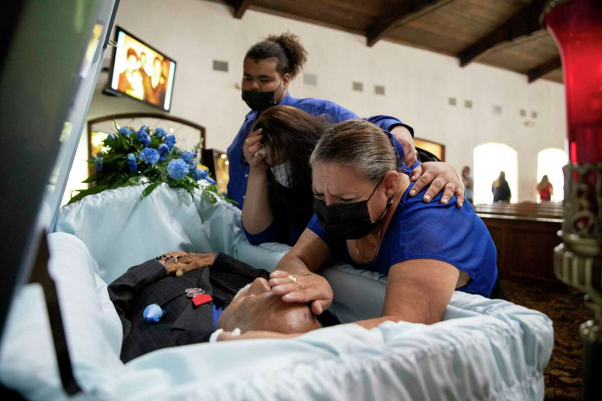 Melinda Hernandez holds her husband, Arturo Ortiz Gonzales Jr., while her daughter Tracy Cruz and grandson Darius Cruz embrace her. Gonzales, 76, died from complications of COVID-19 after being hospitalized for three weeks.
