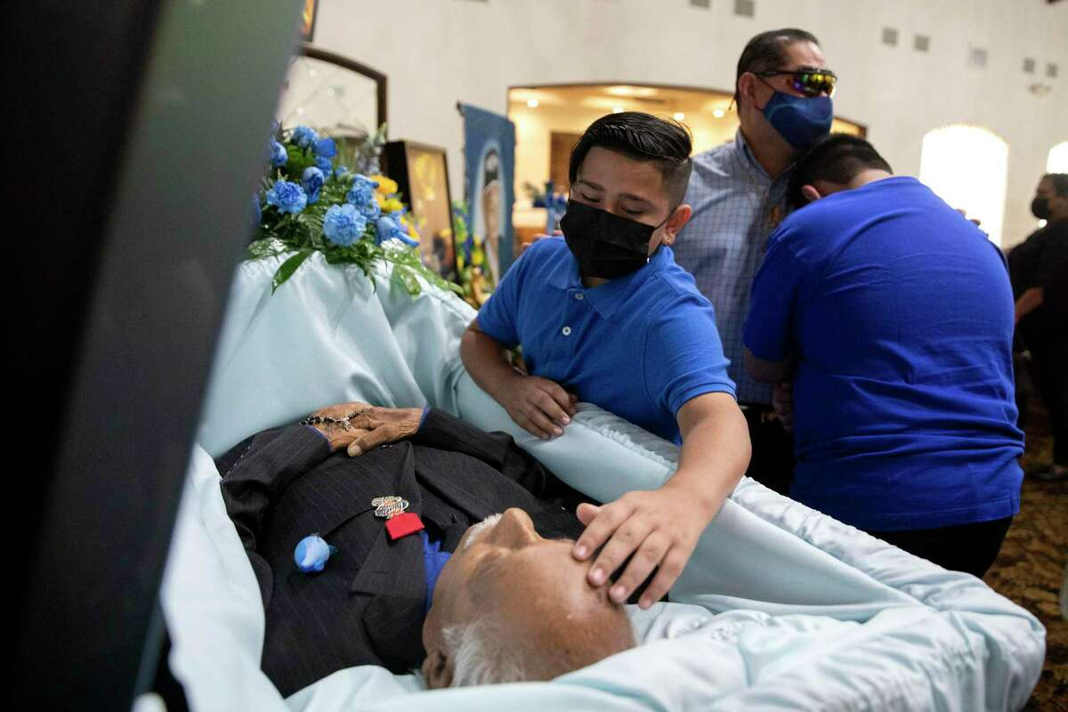 Andrew Gonzales holds his oldest son, Andrew, while his younger son, Aiden, says his final goodbye to Arturo Ortiz Gonzales Jr., one of the more than 4,000 people who have died of COIVD-19 in San Antonio.
