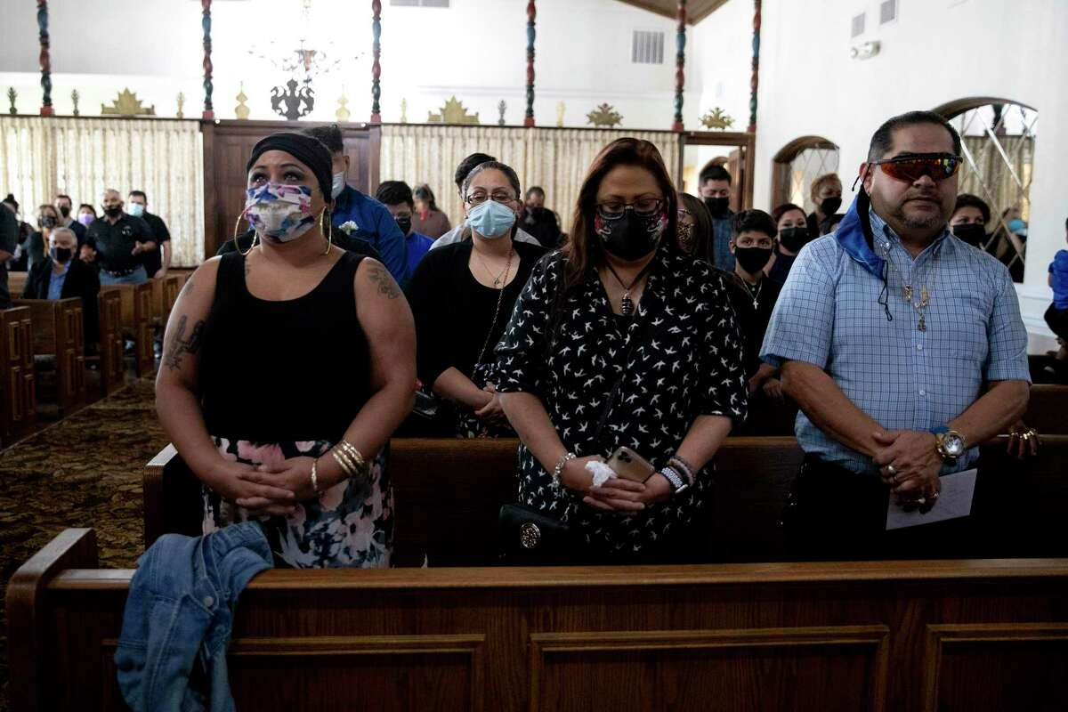Alexis Gonzales, Troylyn Gonzales and Andrew Gonzales pray at the funeral service for Arturo Ortiz Gonzales Jr., who died of COIVD-19.