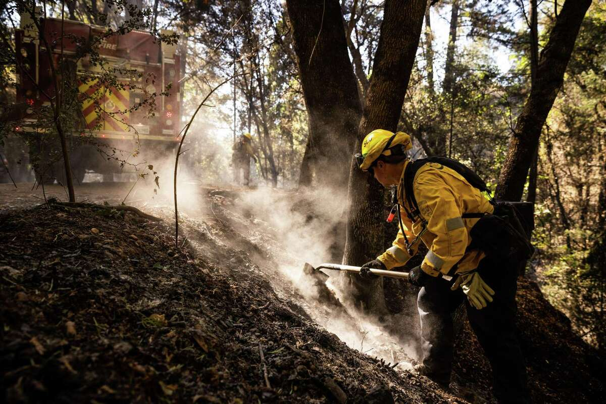 Cal Fire firefighters mop up the River Fire near Colfax, California area on August 5, 2021. The agency said Friday investigators determined the fire was human-caused.