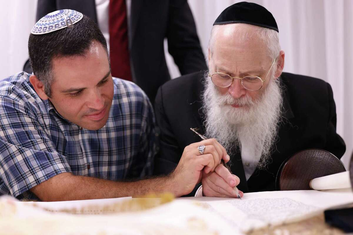 Andrew Friedberg, left, the mayor of Bellaire, participates in the completion of the Unity Torah under the guidance of fifth-generation scribe Rabbi Moshe Klein.