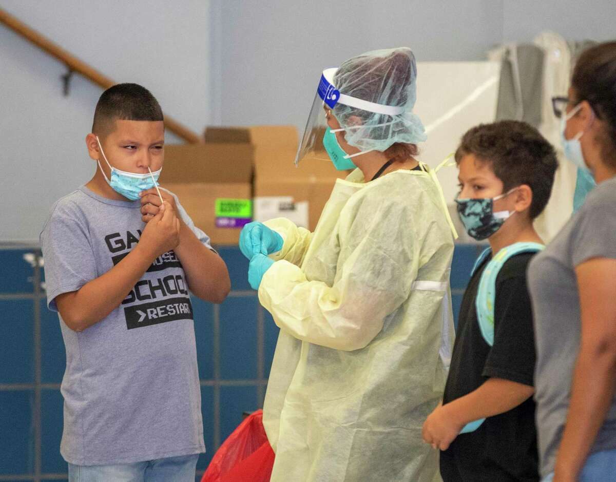 A medical professional oversees a fifth-grader giving himself a rapid coronavirus test in South Gate (Los Angeles County) last month.