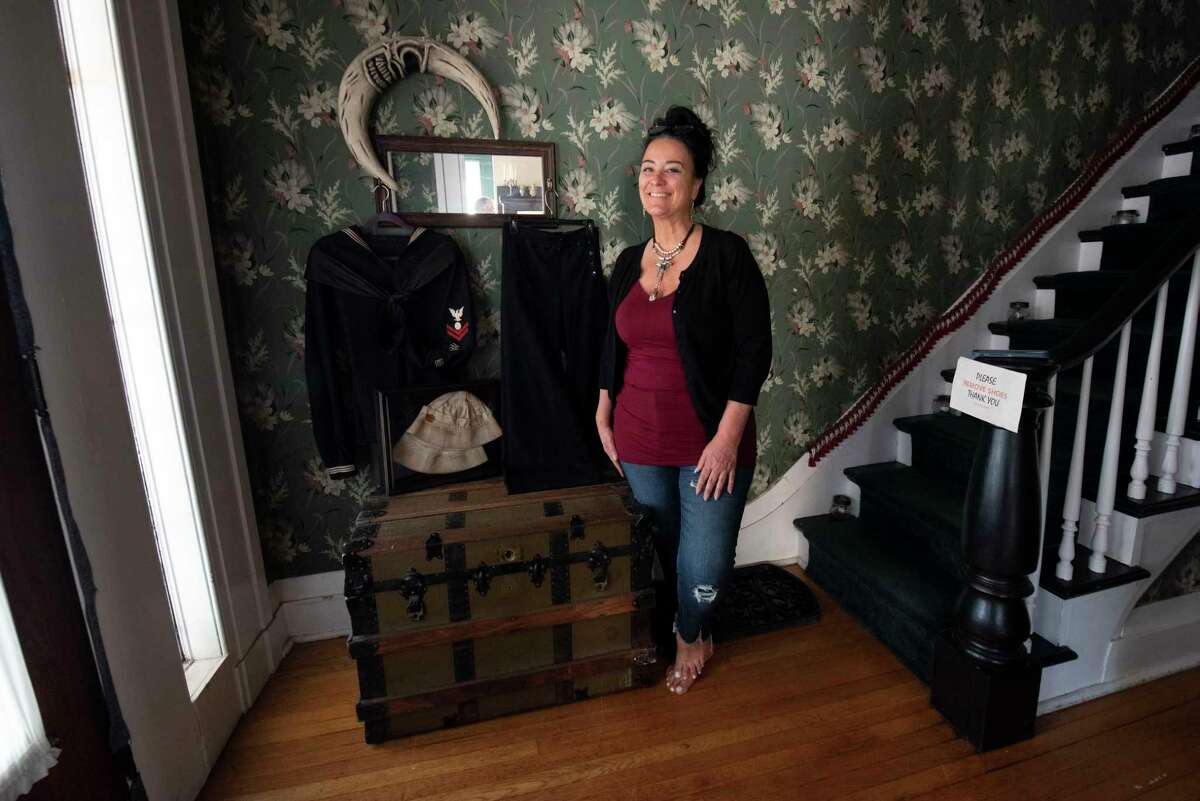 Home owner Michele Bell stands in the Enslin House at 562 Fifth Ave. on Wednesday, Sept. 8, 2021 in Troy, N.Y. The house, considered to be haunted and site of a dinner club where Legs Diamond dined, is for sale for $444,444.