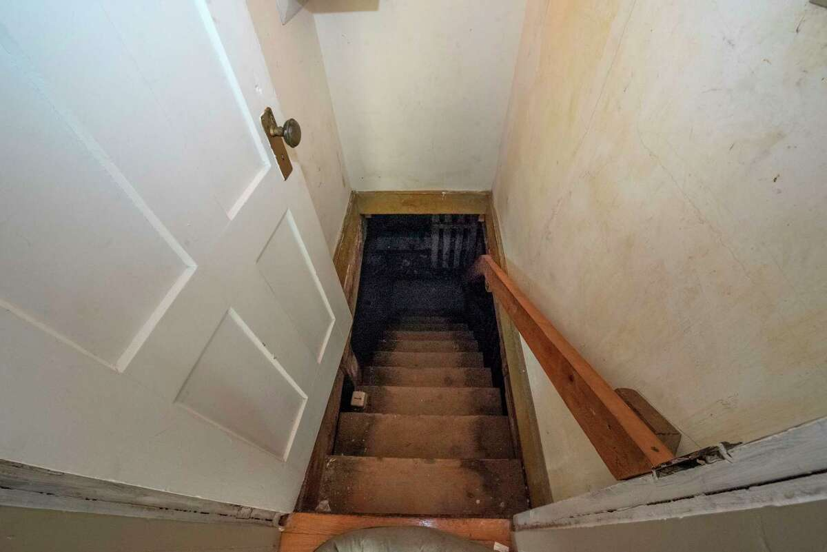 Stairs leading down to the basement of the Enslin House at 562 Fifth Ave. on Wednesday, Sept. 8, 2021 in Troy, N.Y. The house, considered to be haunted and site of a dinner club where Legs Diamond dined, is for sale for $444,444.