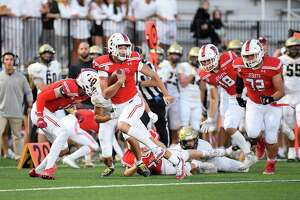 Fairfield Prep QB Connor Smith breaks a tackle to score a first-half touchdown against Daniel Hand on Friday at Rafferty Field in Fairfield.