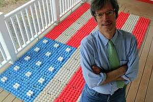 """Robert Carley on the porch of his Darien, Connecticut, home, where he creates flag art out of everyday objects, including egg cartons and eggs (background). Carley just released the art book """"Liberated: Freed from the Flagpole. The Metamorphosis of the Flag Since 9/11."""""""