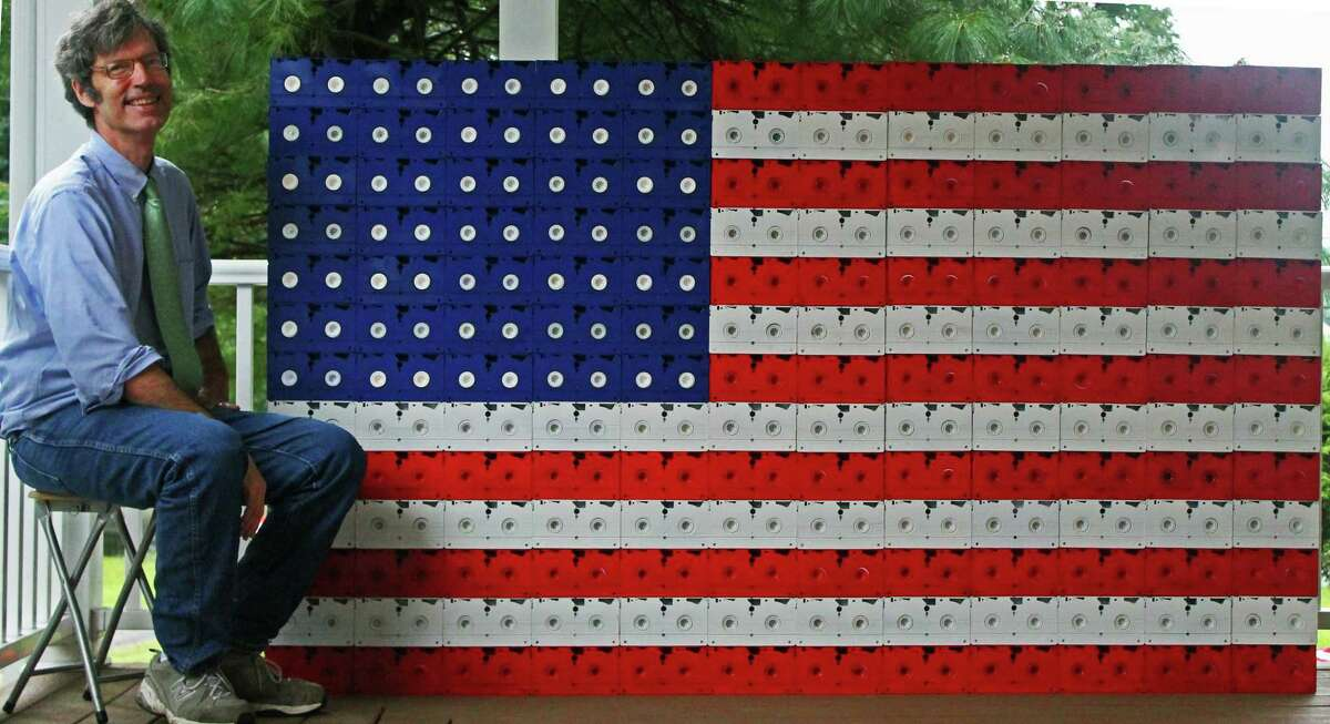 """Robert Carley on the porch of his Darien, Connecticut, home with flag art he created from VHS tapes. Carley just released the art book """"Liberated: Freed from the Flagpole. The Metamorphosis of the Flag Since 9/11."""""""