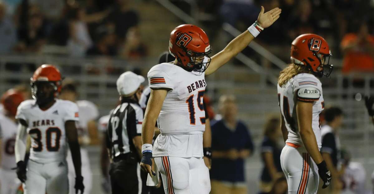 Bridgeland quarterback Conner Weigman (15) signals for first down after being hit out of bounds by The Woodlands defensive linemen John Podowski during the fourth quarter of a non-district high school football game at Woodforest Bank Stadium, Friday, Sept. 10, 2021, in Shenandoah.