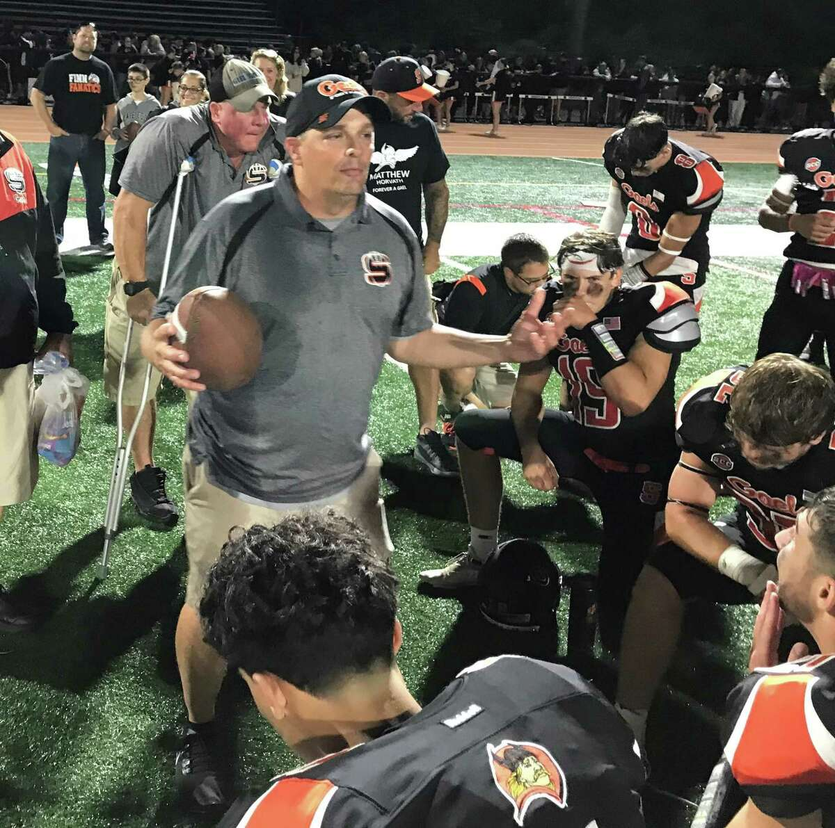 Shelton coach Mike DeFelice addresses his team following Shelton's 23-3 victory against North Haven.
