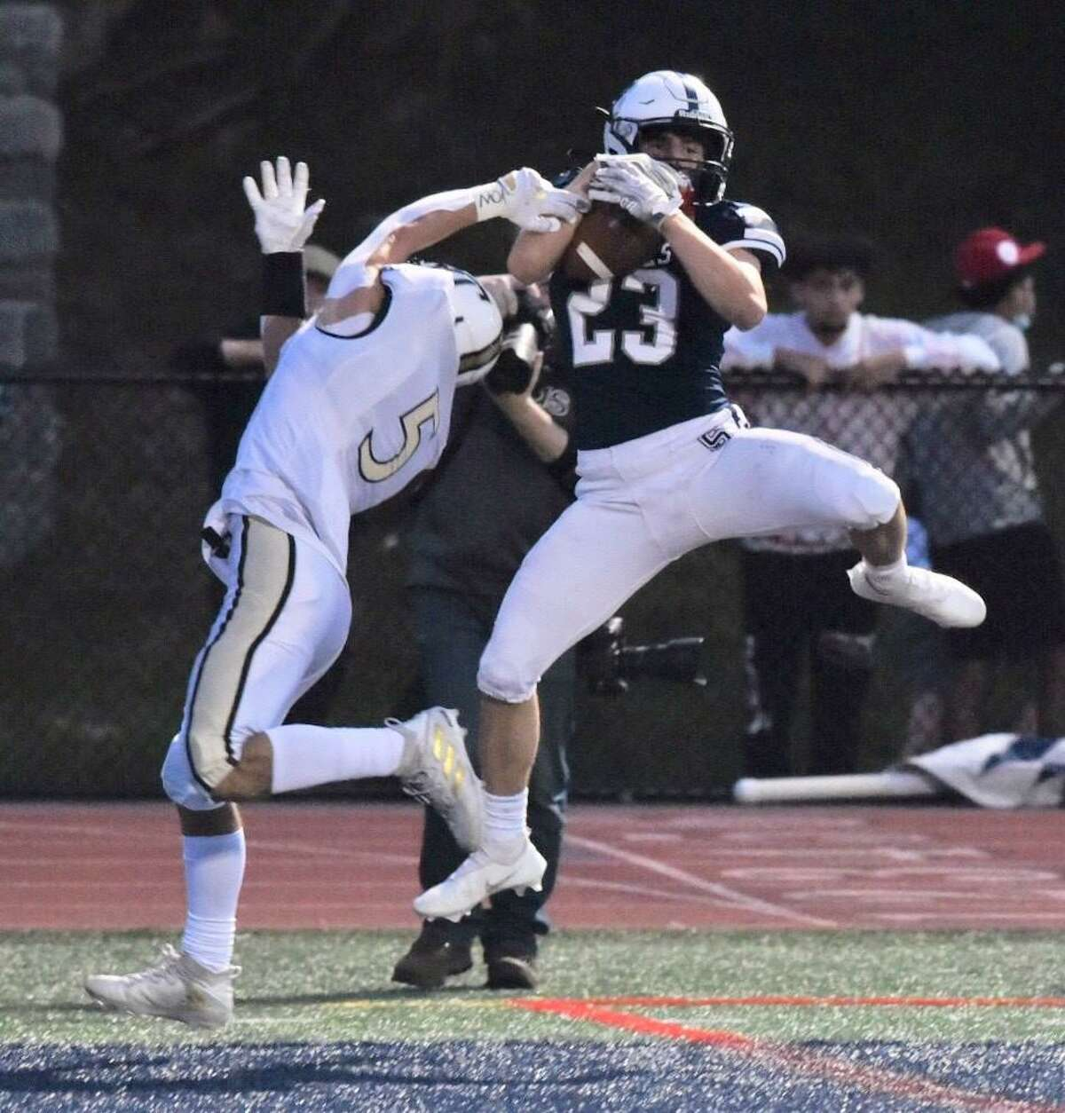Staples' Nick Armentano (23) makes catch while defended by Trumbull's Corbin Smith (5) during a game on Friday in Westport.