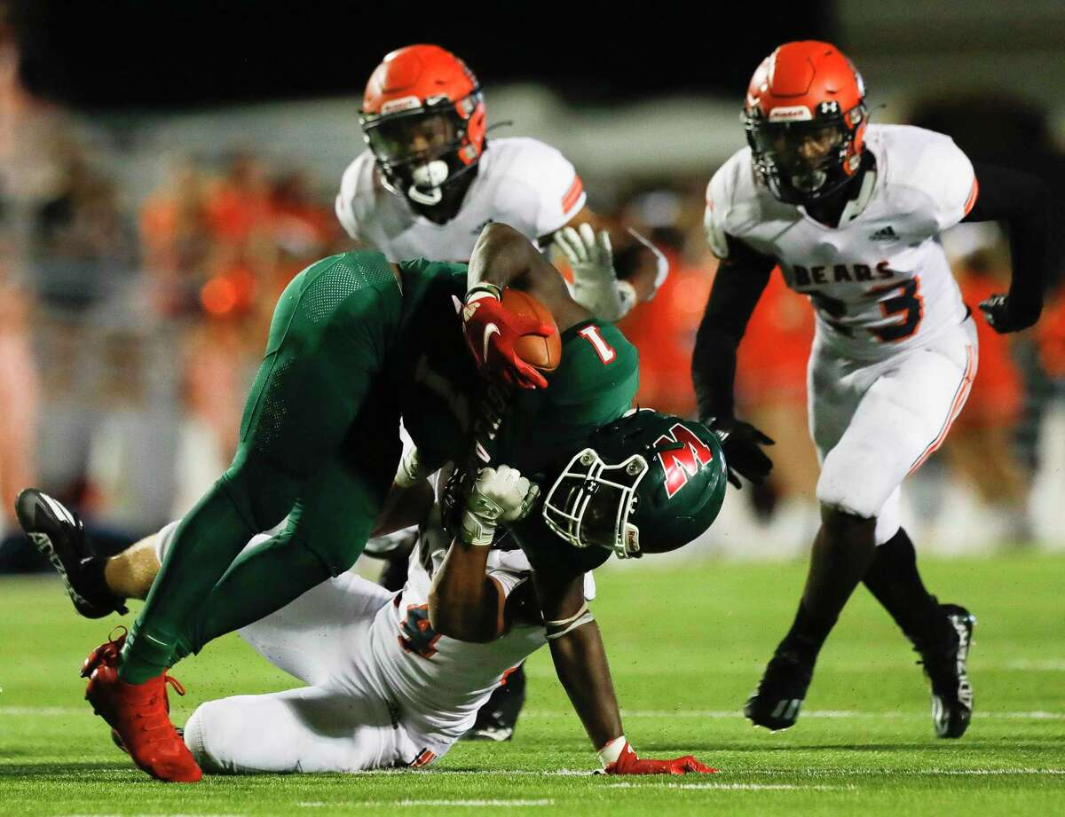 The Woodlands running back JoBarre Reed (1) is dragged down by Bridgeland defensive tackle Nathan Earle (95) during the fourth quarter of a non-district high school football game at Woodforest Bank Stadium, Friday, Sept. 10, 2021, in Shenandoah.