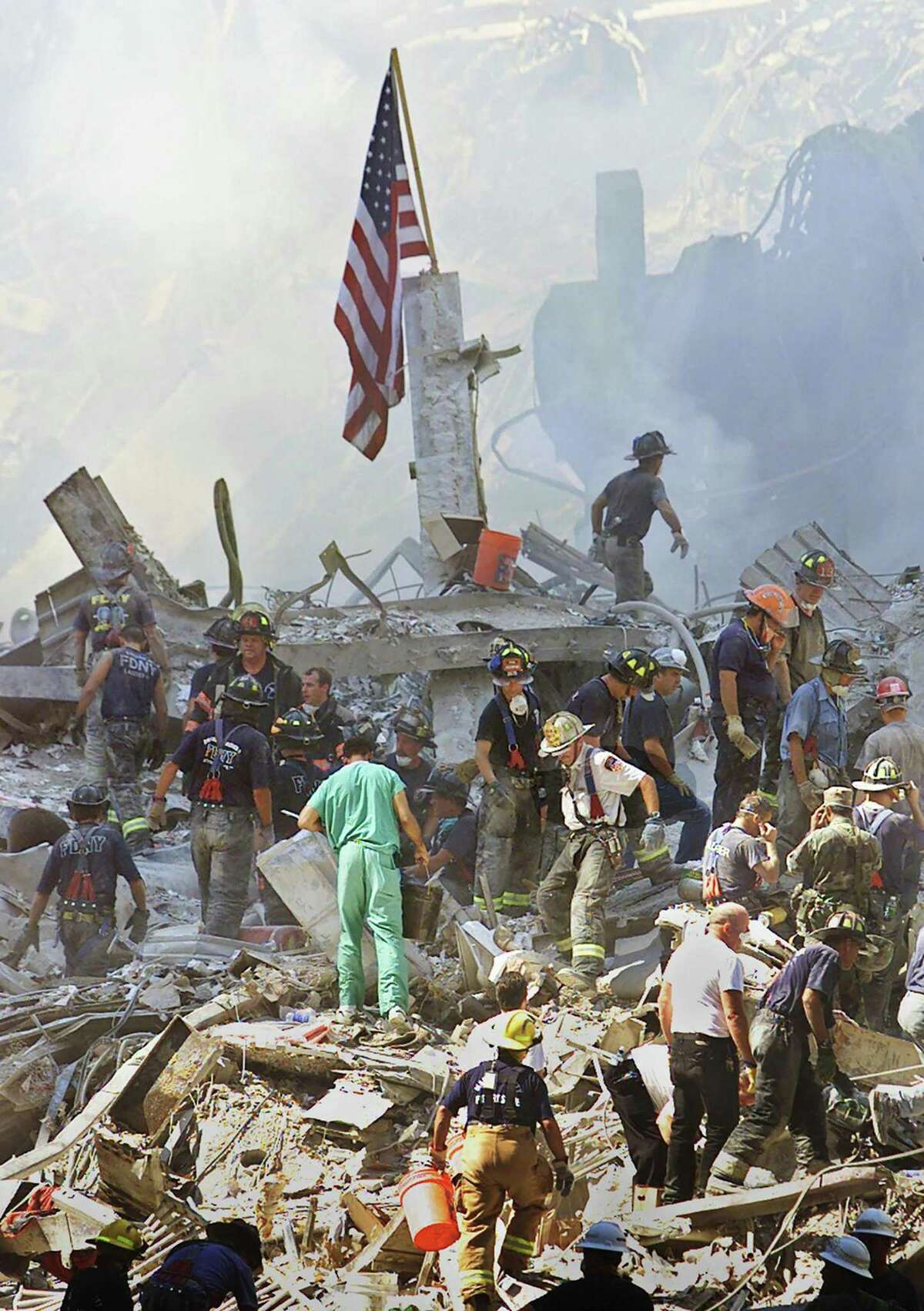 At right, an American flag flies above firefighters and other responders searching the rubble of the World Trade Center two days after the Sept. 11 terrorist attack.