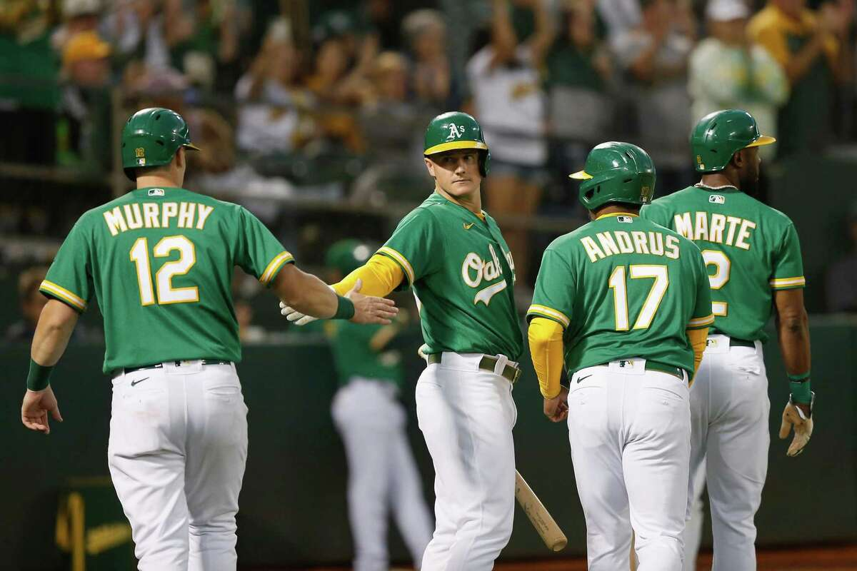 OAKLAND, CALIFORNIA - SEPTEMBER 10: Matt Chapman #26 of the Oakland Athletics celebrates with teammates Sean Murphy #12, Elvis Andrus #17 and Starling Marte #2 after they scored on a three-run single by Matt Olson #28 in the bottom of the second inning against the Texas Rangers at RingCentral Coliseum on September 10, 2021 in Oakland, California. (Photo by Lachlan Cunningham/Getty Images)