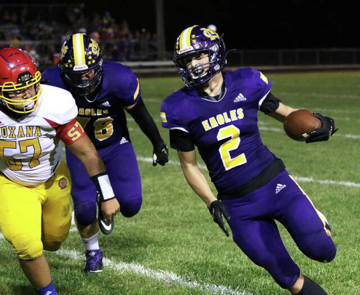 CM's Logan Turbyfill (2) picks up 5 yards before being forced out of bounds by Roxana's Latrell Graves (57) in the second half Friday night at Hauser Field in Bethalto.
