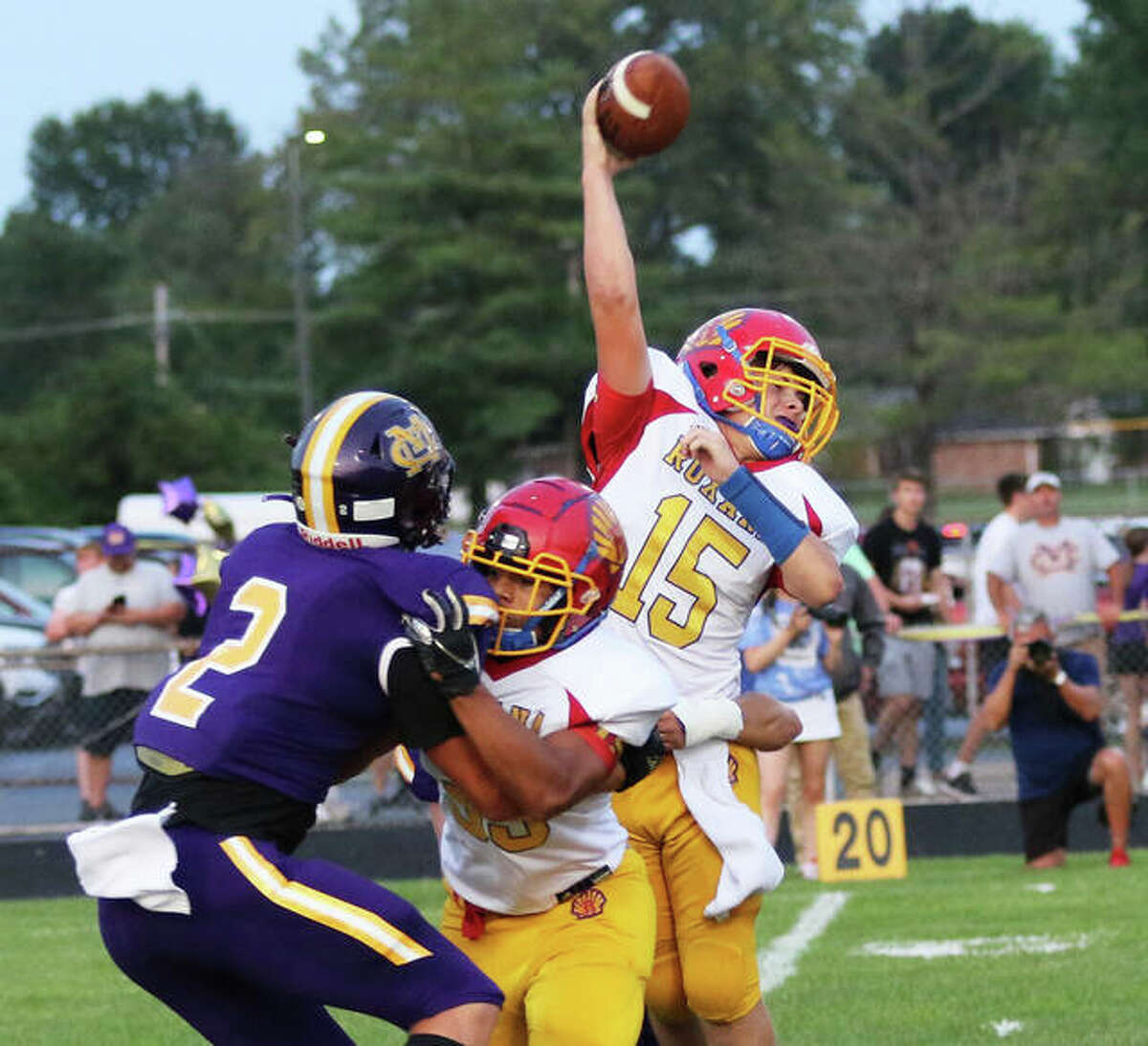 Roxana quarterback Chris Walleck (15) gets off a pass while being hit by CM's Braden Arview while Shells RB Terrel Graves blocks the Eagles' Logan Turbyfill (2) on Friday night at Hauser Field in Bethalto.