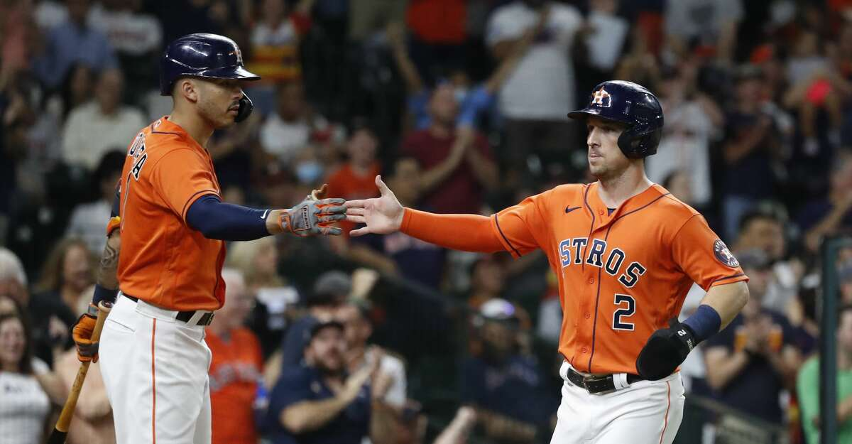 Houston Astros Alex Bregman (2) celebrates with Carlos Correa after scoring a run on Yordan Alvarez's RBI double off of Los Angeles Angels starting pitcher Shohei Ohtani during the third inning of an MLB baseball game at Minute Maid Park, Friday, September 10, 2021, in Houston.