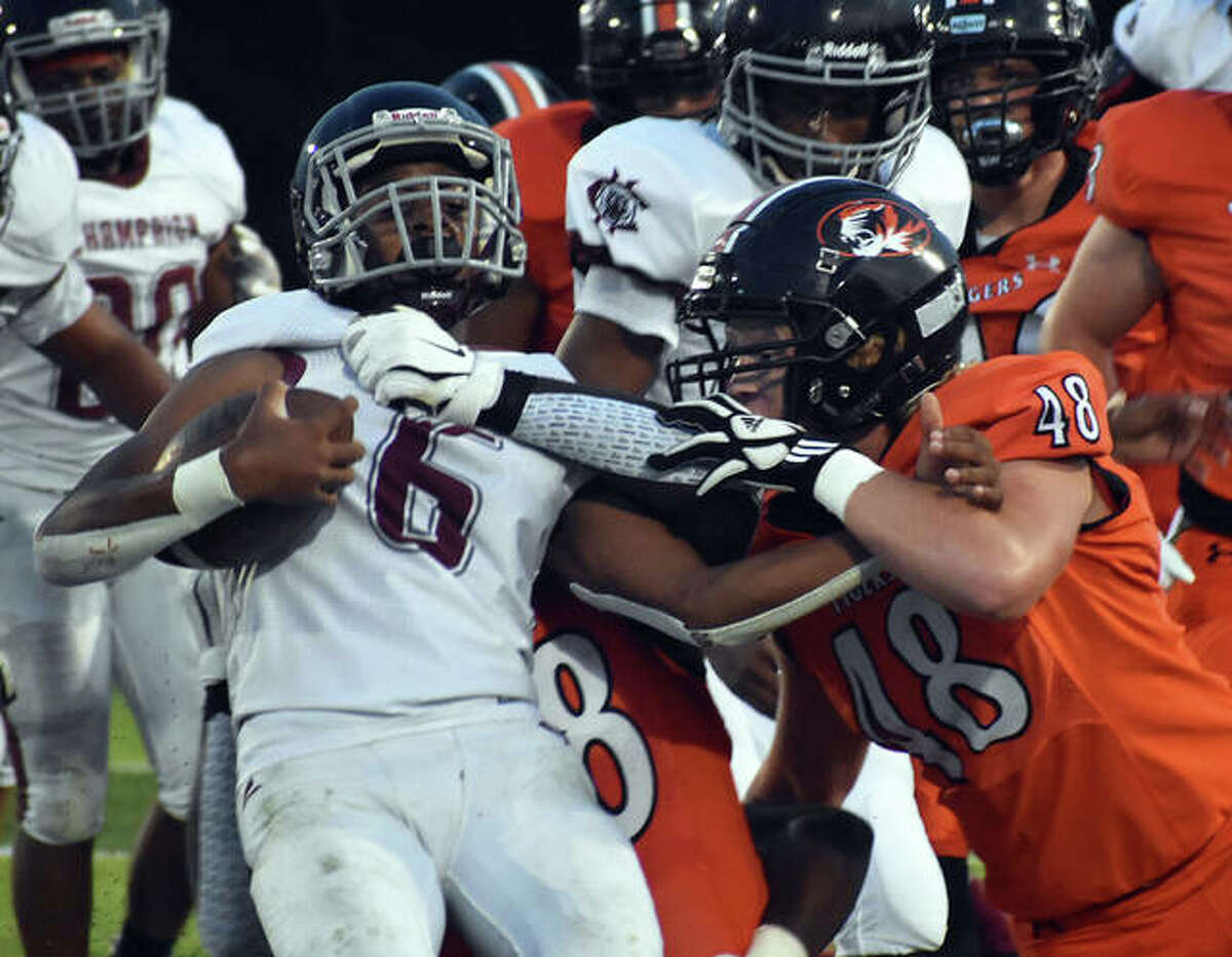 Edwardsville's Wyatt Kolnsberg and Nasim Cairo (not pictured) combine to make a tackle against Champaign Central in the first quarter on Friday in Edwardsville.