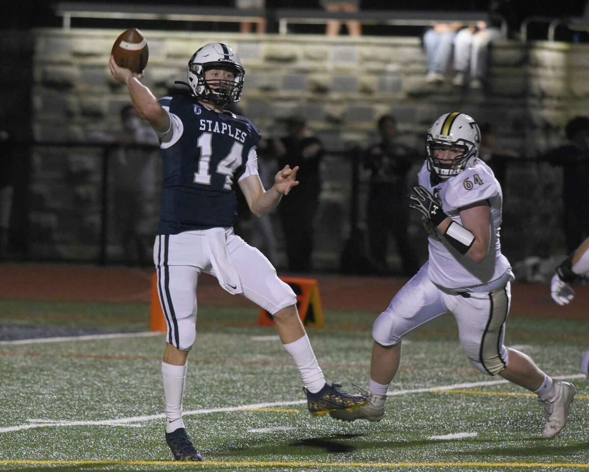 Staples' Ryan Thompson throws a pass while under pressure against Trumbull on Friday in Westport. Staples won 27-20.