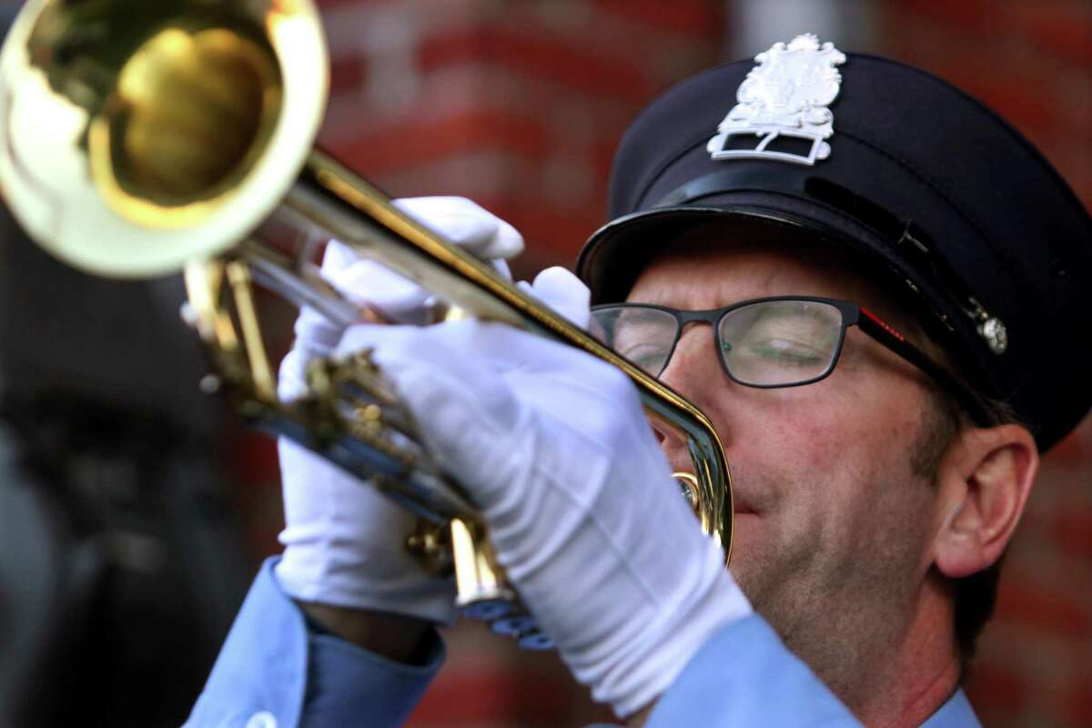 Firefighter Ken Pound plays taps during a ceremony to commemorate the 20th anniversary of 9/11 at Glenville Volunteer Fire Company in Greenwich, Conn., on Friday September 10, 2021.