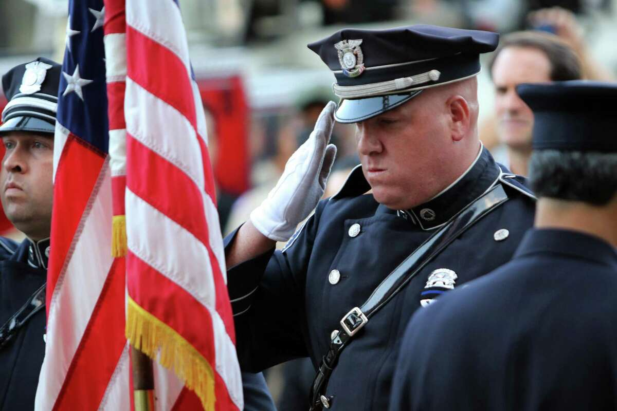 A member of the Greenwich Police Department Honor Guard salutes the U.S. flag during Glenville Volunteer Fire Company's ceremony to commemorate the 20th anniversary of 9/11 in Greenwich, Conn., on Friday September 10, 2021.