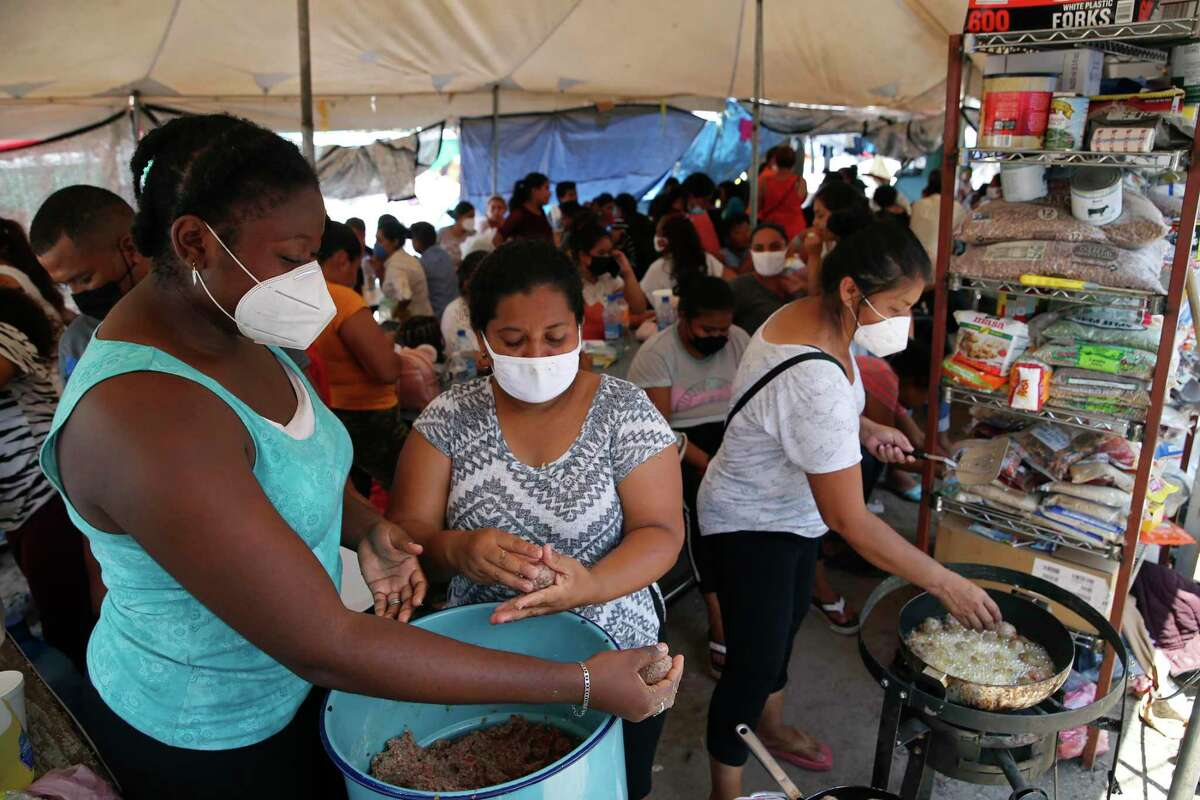 Migrant women cook food July 26 for a crowd camped out at Plaza de la Republica in Reynosa, Mexico. The U.S. is still enforcing Title 42 travel restrictions/