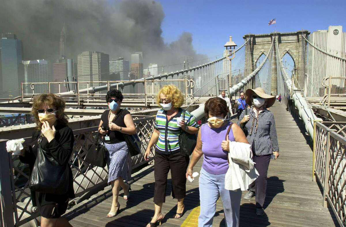 Women wearing dust masks flee across the Brooklyn Bridge from Manhattan to Brooklyn following the collapse of both World Trade Center towers Tuesday, Sept. 11, 2001 in New York.