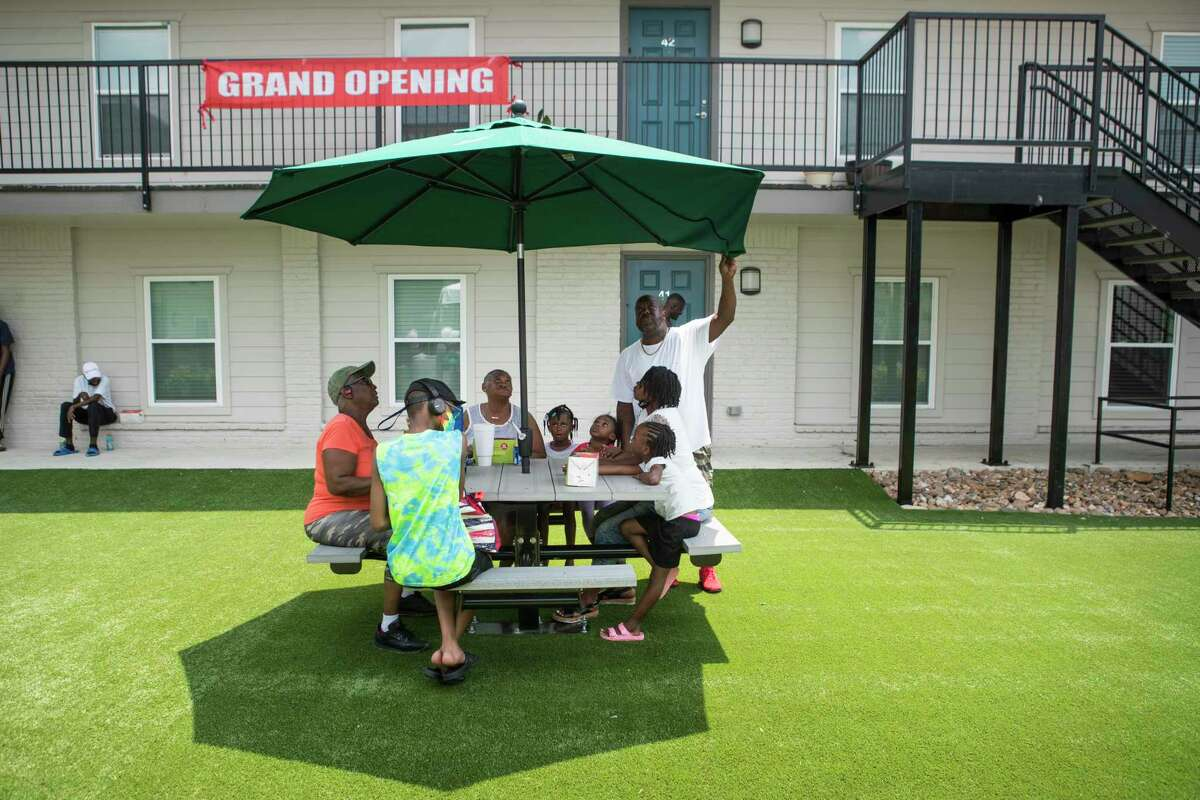 Residents of Bellfort Park Apartments gather around a picnic table during the grand reopening of the complex Wednesday, July 28, 2021 in Houston. Bellfort Park was the first development announced through the Harvey Multifamily Program, the first to be approved by City Council - and now the first to reopen to residents.