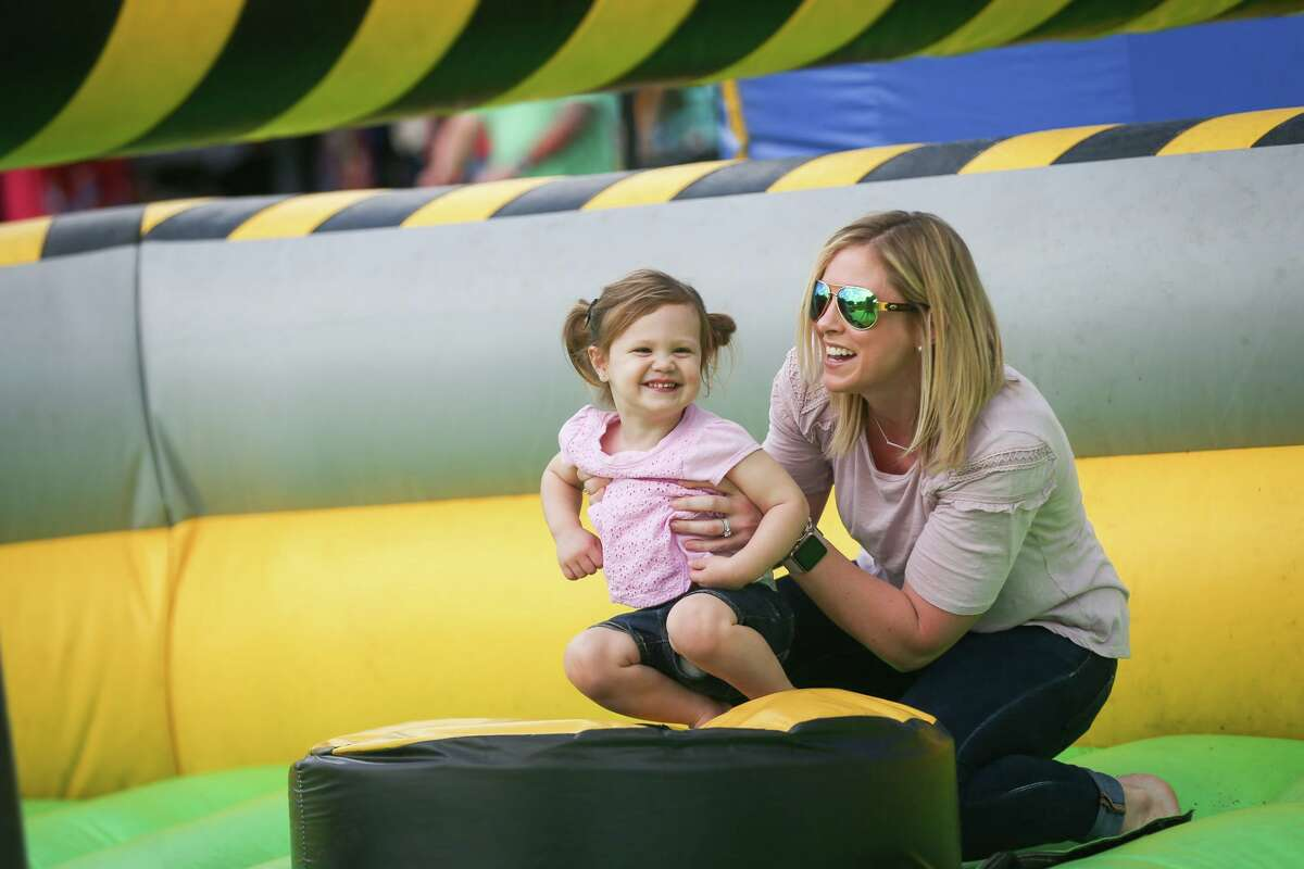 The Woodlands Family Fun Fest presented by Houston Area Shows is scheduled for Sept. 18 at Town Green Park in The Woodlands. Here, Lindsay Mobley ducks under a rotating arm with her daughter Landry, 2, while in an inflatable play area during The Woodlands Family Fun Fest on Saturday, March 18, 2017.