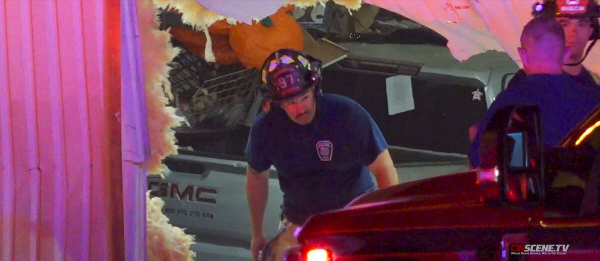Emergency responders aid a man who had to be life flighted after crashing his vehicle into the side of Top Dog Halloween store on .