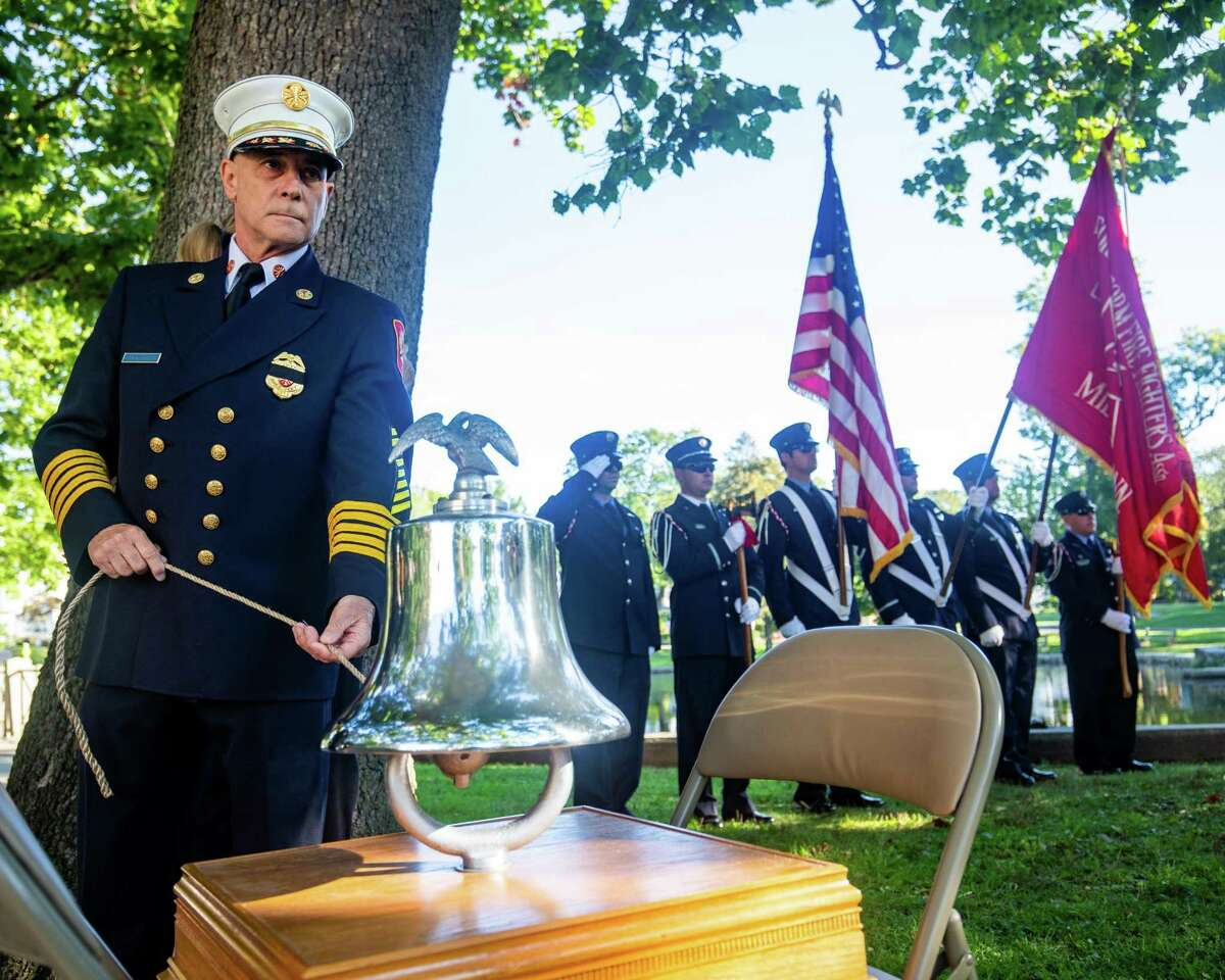 Milford Fire Department Chief Douglas Edo rings a bell for the three Milford residents killed in the September 11 attacks on the World Trade Center during the Milford 9/11 ceremony at Milford City Hall on Saturday, September 11, 2021.