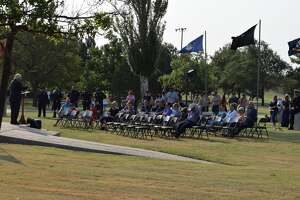 Citizens gather around the flag pole at Kidsville for a special 9/11 Memorial Event hosted by the city of Plainview on Sept. 11, 2021.