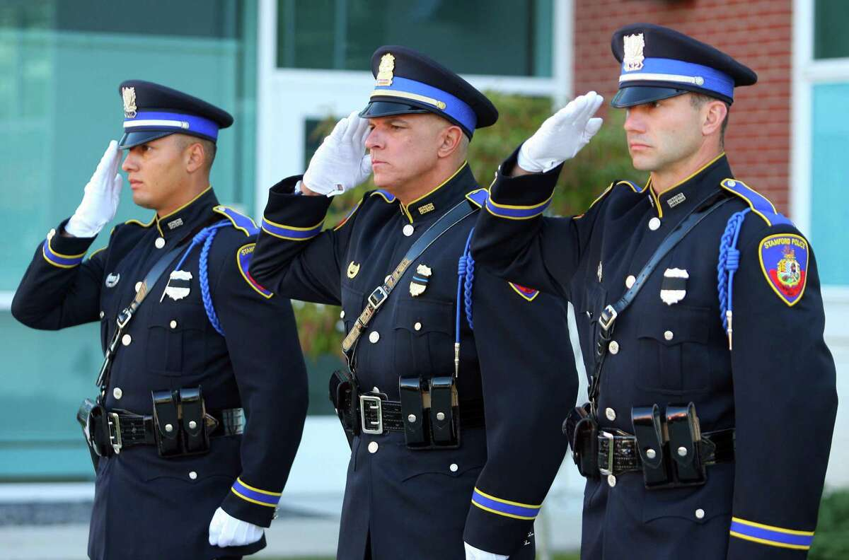 Stamford Police Officers Damein Rosa, left, Lieutenant Douglas Deiso, and Sergeant Kevin Lynch, right, salute during a 9/11 memorial on the 20th anniversary of the terrorist attacks in front of police headquarters in Stamford, Conn., on Saturday September 11, 2021.