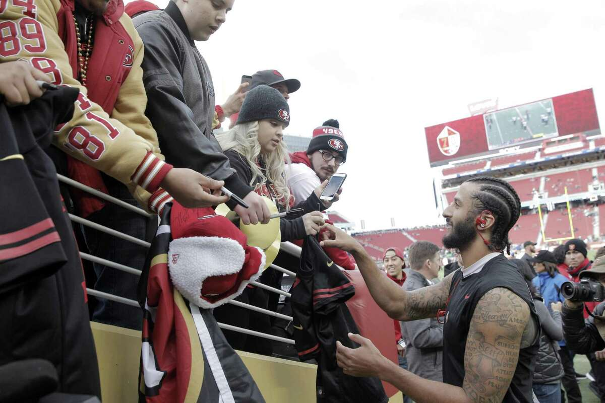 Colin Kaepernick (7) signs autographs after warming before the San Francisco 49ers played the Seattle Seahawks at Levi's Stadium in Santa Clara, Calif., on Sunday, January 1, 2017.