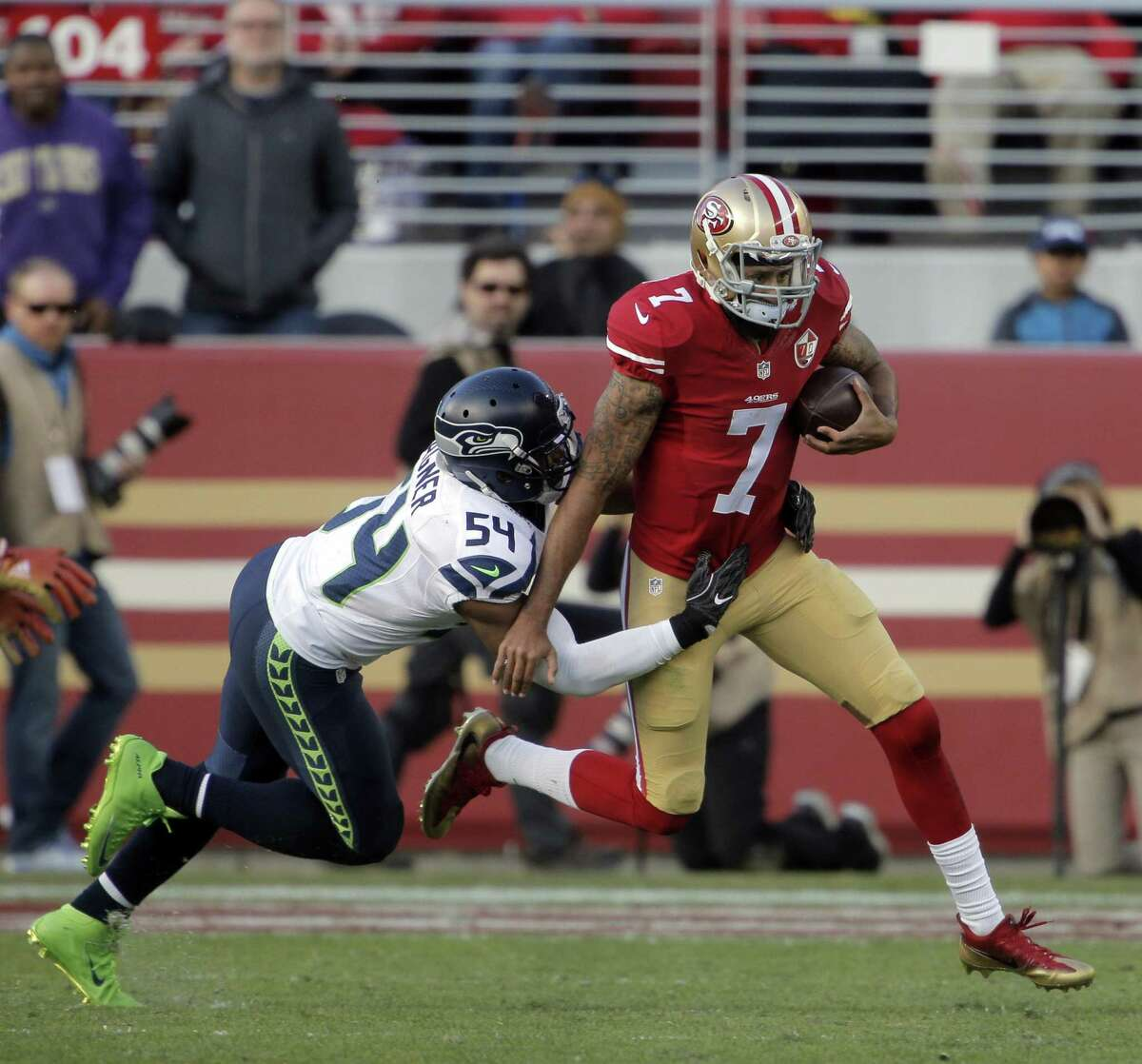 Colin Kaepernick (7) scrambles under pressure from Bobby Wagner (54) in the first half as the San Francisco 49ers played the Seattle Seahawks at Levi's Stadium in Santa Clara, Calif., on Sunday, January 1, 2017.