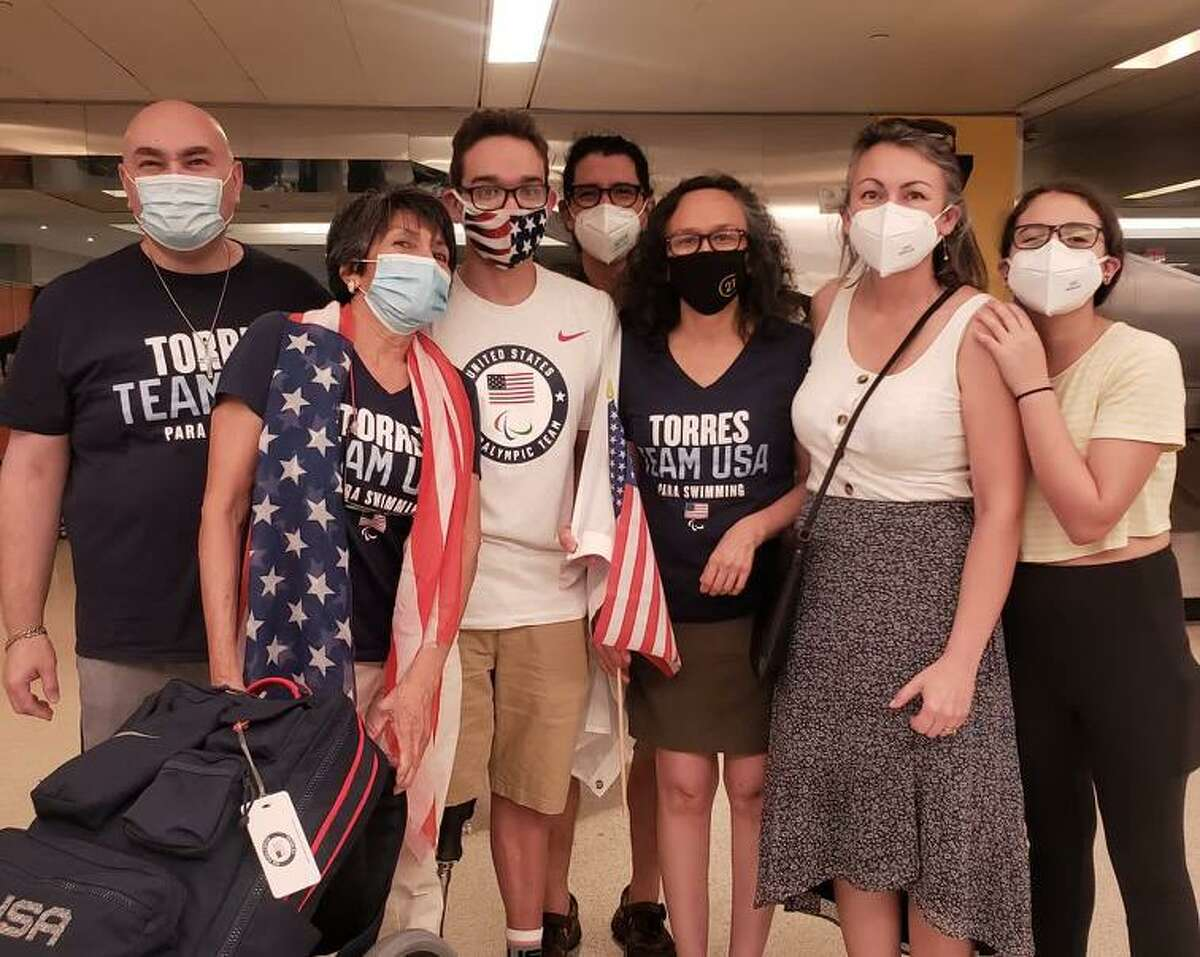 Matthew Torres (center with flag mask) is welcomed home from the 2020 Paralympics by his dad, Gil, (far left) and mom, Martha (right of Matthew in black mask) along with close friends at the Newark Liberty International Airport in New Jersey. Matthew won a bronze medal at the 2020 Summer Games in the 400-meter S8 freestyle.